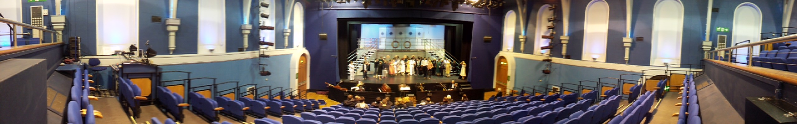 Panoramic view of the stage from the rear centre of the auditorium stalls with the sound mix position in view rear of stalls left in working light with the cast on stage in costume getting notes