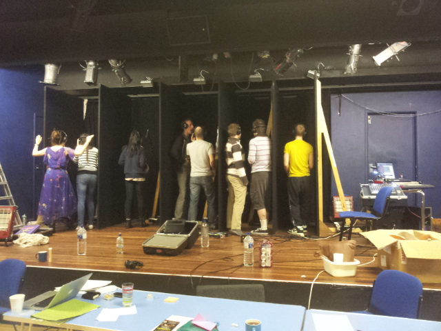 make shift vocal recording booths made from scene flats and backdrop curtains with actors singing into the microphones